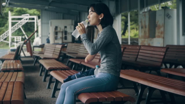medium shot of a female adaptive athlete taking a break during training at an athletics track - fare una pausa video stock e b–roll