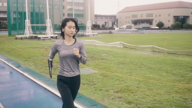 medium shot of a female adaptive athlete training for competition at a university athletics stadium - sports training点の映像素材/bロール