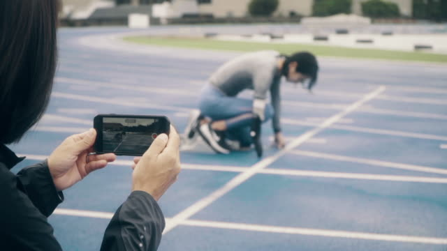 medium shot of a female adaptive athlete training with her coach at an athletics track starting line - artificial limb stock videos & royalty-free footage