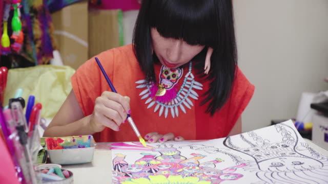 彼女の折衷的なアートスタジオで女性アーティストの絵画のミディアムショット - デザイナー点の映像素材/bロール