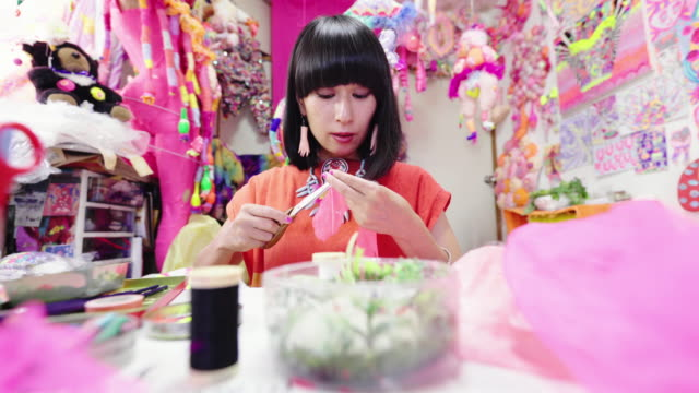 vidéos et rushes de tir moyen d'une artiste femelle enfilant une aiguille à coudre dans son studio d'art éclectique - décalé