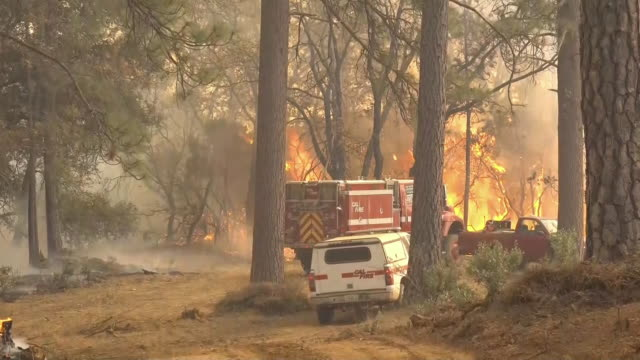 medium shot of a firetruck and other emergency vehicles near a burning wildfire in paradise, california on november 18, 2018. - fire engine stock videos & royalty-free footage