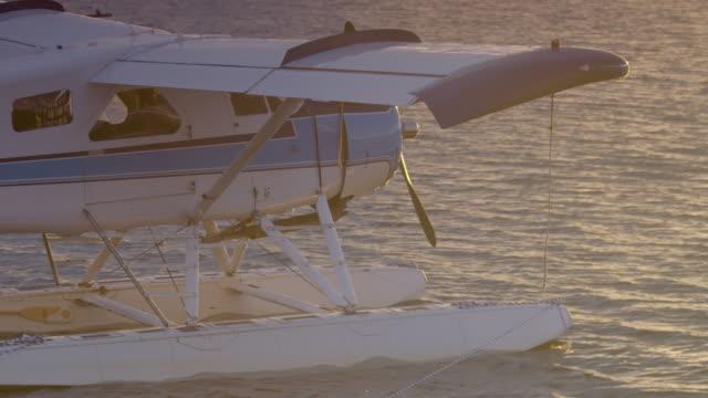 medium shot of a float plane docked on iliamna lake - 水上飛行機点の映像素材/bロール