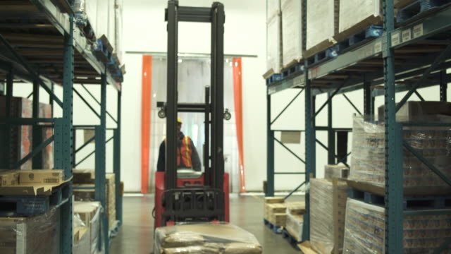 medium shot of a forklift driver transporting product - only mature men stock videos and b-roll footage
