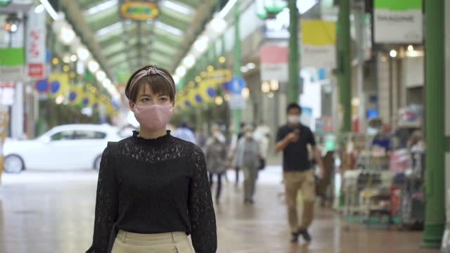 vídeos y material grabado en eventos de stock de medium shot of a generation z aged woman shopping with a protective face mask on in a marker area - generation z