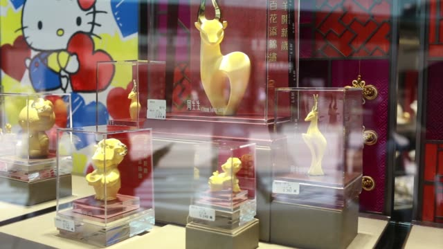 vidéos et rushes de medium shot of a golden goat displayed outside a chow sang sang holdings international ltd jewelry store in the mong kok district of hong kong china... - mong kok