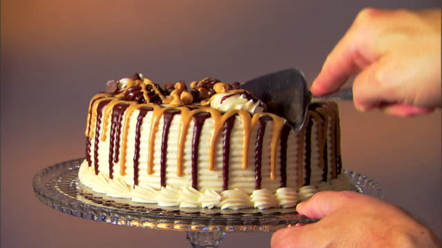 Medium shot of a hand slicing and lifting a slice of cake.