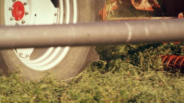 medium shot of a hay baler as seen from behind a wheel irrigation system - プロボ点の映像素材/bロール