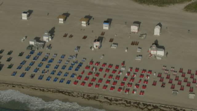 medium shot of a hotel staff placing colorful cushions on beach chairs - seaweed stock videos & royalty-free footage