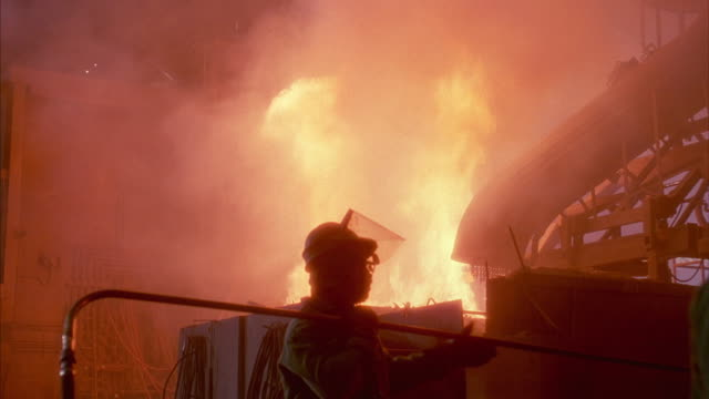 Medium shot of a machine in a fiery foundry with sparks and smoke.
