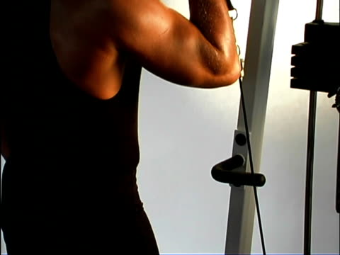 medium shot of a male's arm lifting a weight on a bicep curl machine. the camera then tilts up to his face. - arm curl stock videos and b-roll footage