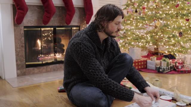 medium shot of a man tying a bow on a gift for christmas - auf dem boden sitzen stock-videos und b-roll-filmmaterial
