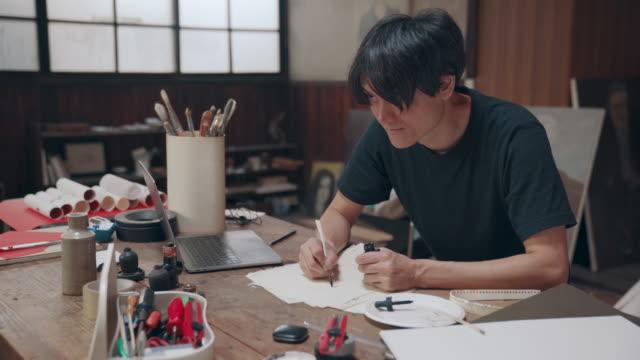 vídeos y material grabado en eventos de stock de medio plano de un artista masculino madura bosquejar ideas en su estudio - pintor