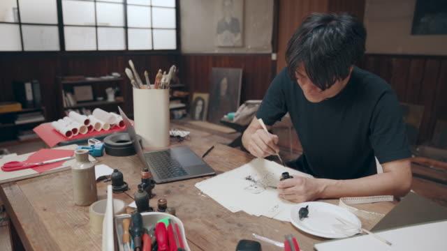 成熟した男性アーティストの彼のスタジオのアイデア スケッチのミディアム ショット - 画家点の映像素材/bロール