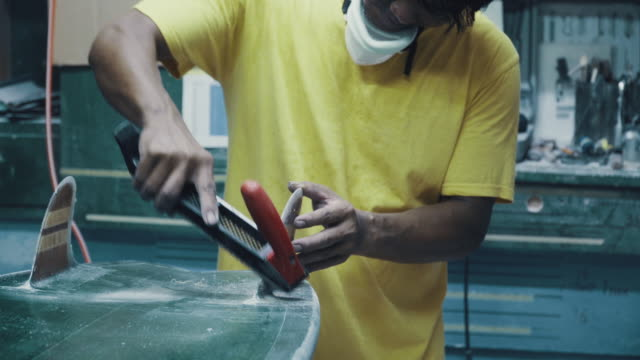 medium shot of a mature man shaping and polishing a surfboard by hand in his small business surf shop - molding a shape stock videos & royalty-free footage