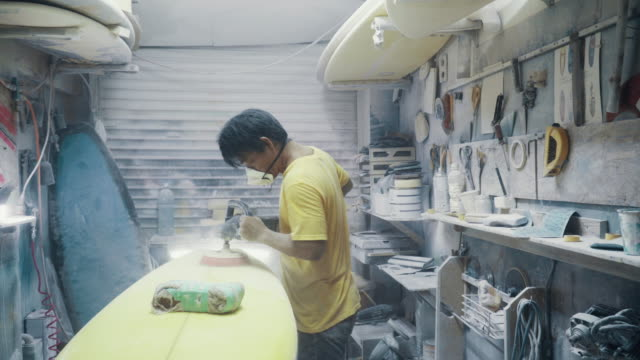 medium shot of a mature man shaping and polishing a surfboard by hand in his small business surf shop - effort stock videos & royalty-free footage