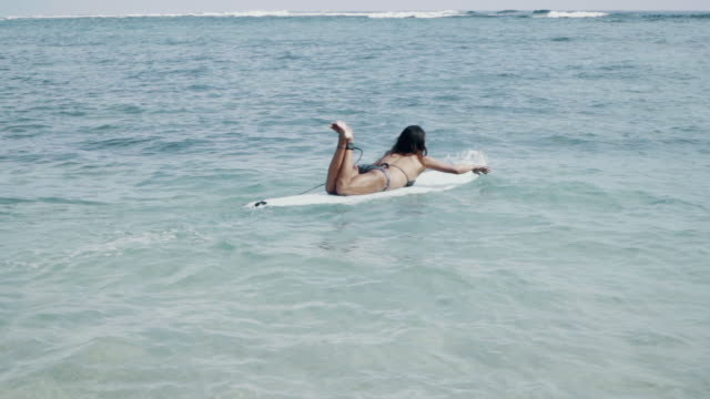 medium shot of a mature woman paddling out to go surfing - サーフボード点の映像素材/bロール