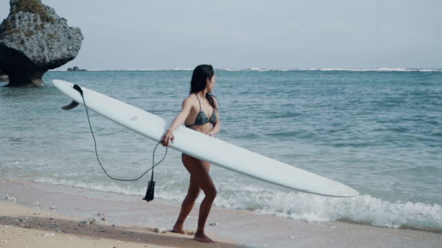 medium shot of a mature woman walking along a beach with a surfboard while looking out over the ocean - サーフボード点の映像素材/bロール
