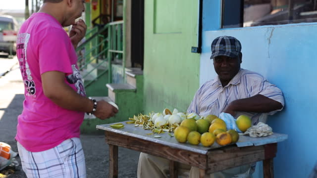 santo domingo dominican republic november 30 2012 a medium shot of a men sitting on a table which is functioning as a small market stand with plenty... - santo domingo dominican republic stock videos & royalty-free footage