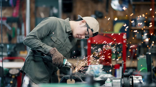 medium shot of a mid adult male using a machine grinder to while working on a piece of metal - steel stock videos & royalty-free footage