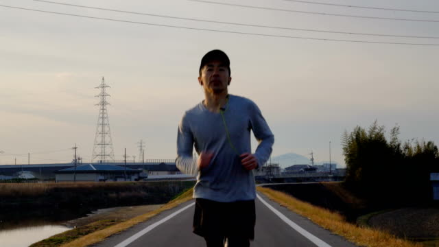 medium shot of a mid adult man running in the morning - males stock videos & royalty-free footage