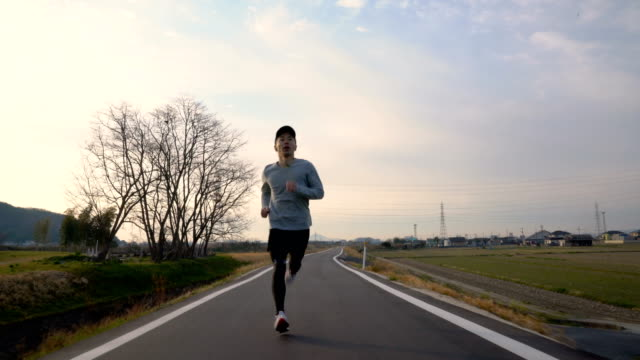 medium shot of a mid adult man running in the morning - giapponese video stock e b–roll