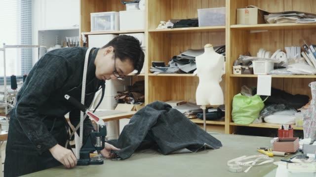 vidéos et rushes de tir moyen d'un tailleur mi-adulte travaillant dans son studio de design créant des produits en denim - jeans
