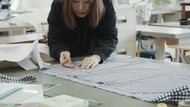 彼女のデザインスタジオで働いているミッドアダルトのテキスタイルアーティストのミディアムショット - ファッションデザイナー点の映像素材/bロール