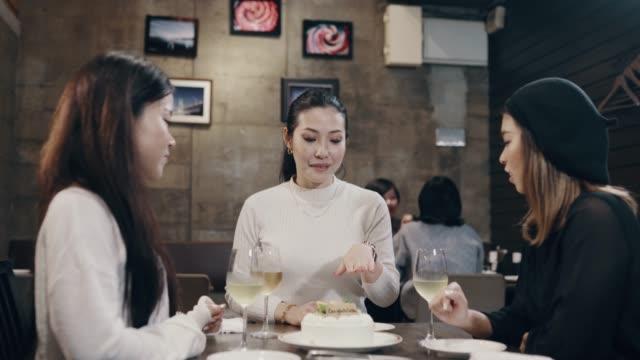 Medium shot van een mid volwassen vrouwen tonen haar nieuwe bruiloft verlovingsring aan haar vrienden in een restaurant