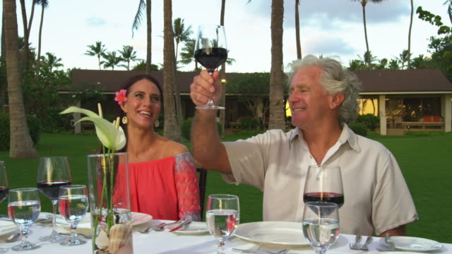 medium shot of a middle-aged man giving a toast to his friends at the dinner table while dining outside - kahuku stock videos & royalty-free footage