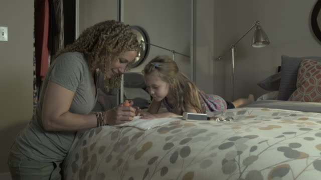 stockvideo's en b-roll-footage met medium shot of a mother painting the nails of her daughter - dubbel bed