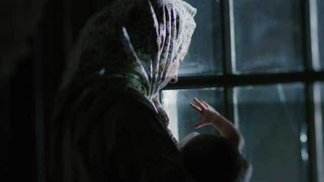 vidéos et rushes de medium shot of a newborn baby held by a woman in front of the window - image du xviiième siècle