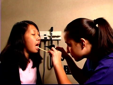 Medium shot of a nurse checking a teen girl's mouth during a visit to the doctor.