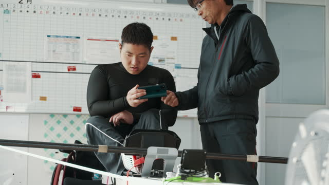medium shot of a paraplegic athlete and his coach reviewing video footage on a smartphone while training in a gym - paraplegic stock videos & royalty-free footage