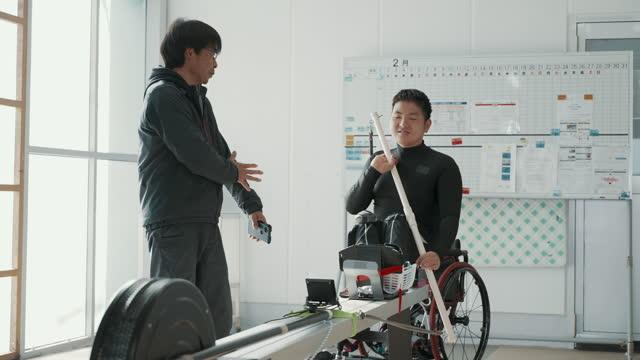 medium shot of a paraplegic athlete training in a gym with his coach - paraplegic stock videos & royalty-free footage