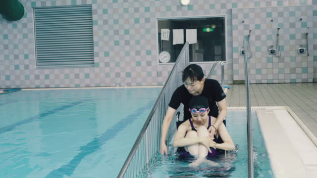 medium shot of a paraplegic woman in a wheelchair and her coach entering or leaving the pool before or after training for competitive swimming - 障がい点の映像素材/bロール
