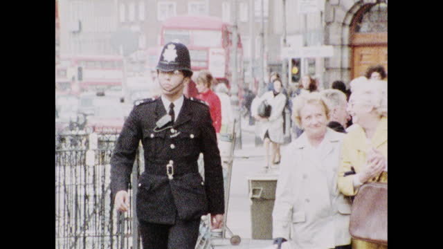medium shot of a policeman in uniform walking towards the camera while on patrol in lewisham, london; 1973. - capital cities stock videos & royalty-free footage