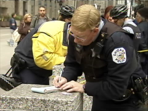 medium shot of a policeman writing tickets for seniors and their young supporters during a mass arrest at 'occupy chicago' senior citizens gathered... - anonymous activist network stock videos & royalty-free footage