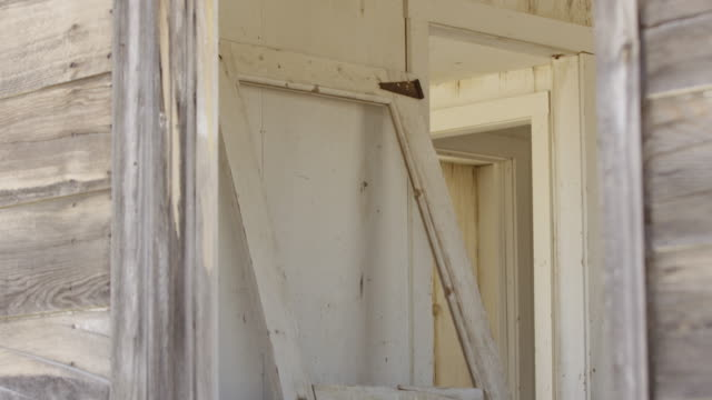 medium shot of a ruined house interior through a window at nevada test site - nevada stock-videos und b-roll-filmmaterial