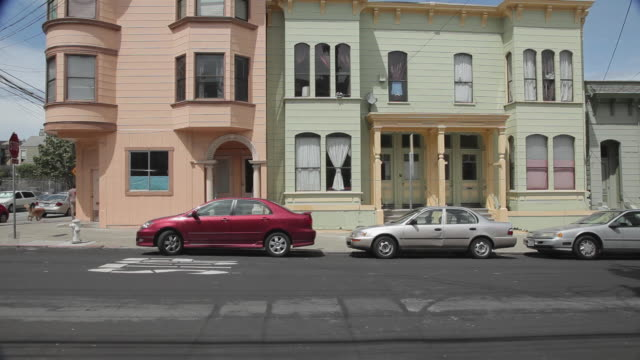 Medium Shot of a school bus passing in front of houses in San Francisco