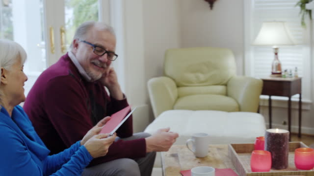 Medium shot of a senior couple opening a greeting card