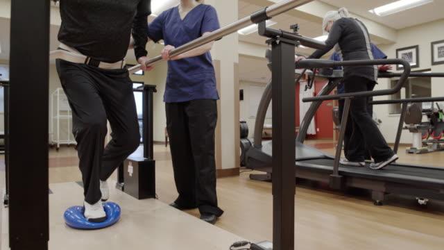 medium shot of a senior man doing stability exercise - auf einem bein stock-videos und b-roll-filmmaterial