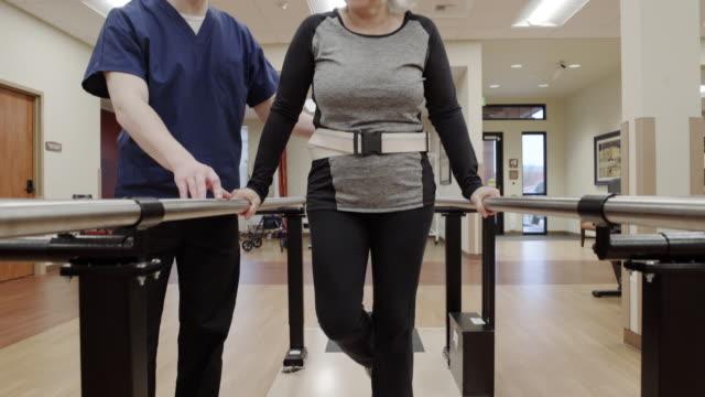 medium shot of a senior woman doing stability exercise - auf einem bein stock-videos und b-roll-filmmaterial
