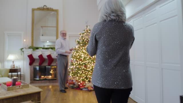 vídeos de stock e filmes b-roll de medium shot of a senior woman giving a gift to her husband - plano geral