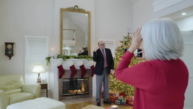 medium shot of a senior woman taking a photo of her husband - christmas stocking stock videos and b-roll footage