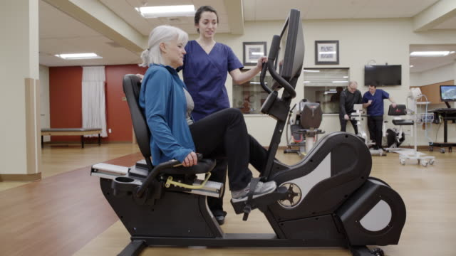 vidéos et rushes de medium shot of a senior woman using a rehabilitation bicycle - montrer la voie