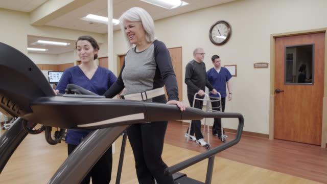 Medium shot of a senior woman walking on a rehabilitation treadmill