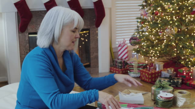 Medium shot of a senior woman wrapping a gift for Christmas
