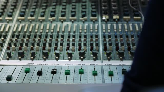 vidéos et rushes de medium shot of a sound mixing desk in use - matériel d'enregistrement