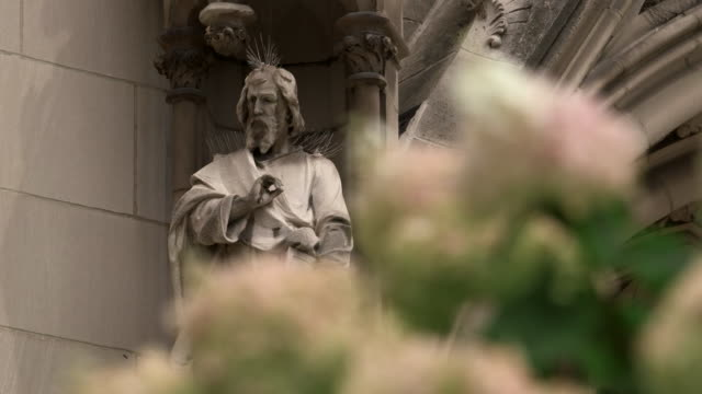 medium shot of a statue outside of saint paul cathedral with flowers in the foreground on august 15, 2018 in pittsburgh, pennsylvania. - religion or spirituality stock videos & royalty-free footage